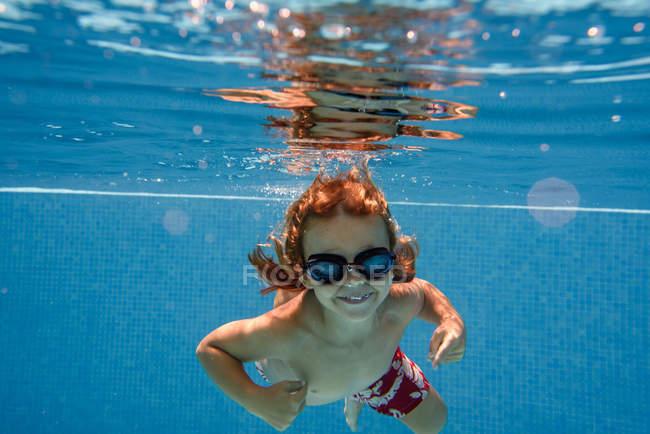 Suchen Sie in der Kamera beim Schwimmen unter Wasser in blauen Pool vorschulkind — Stockfoto