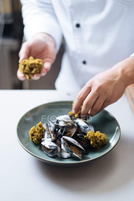 Крупным планом шеф-повара в белые единообразного тарелку северных морепродуктов с мидиями на плите — стоковое фото
