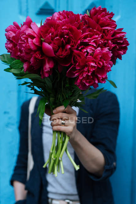 Woman holding bouquet of pink peonies in front of face on blue background — Stock Photo