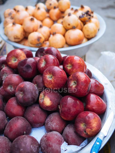 Bowls of fresh apples and pomegranates at farmer market — Stock Photo