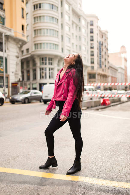 Trendy young woman in pink leather jacket laughing on street — Stock Photo
