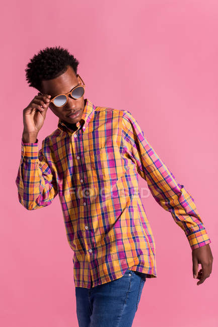 Stylish hipster man in checkered sunglasses and shirt on pink background — Stock Photo