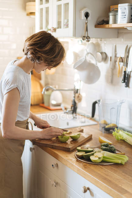 Frau, die Äpfel schneiden und Vorbereiten der gesunde Teller mit grünen Früchte und Gemüse auf Holz Küchentisch — Stockfoto