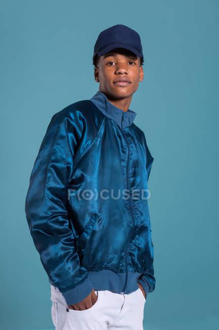 Trendige ethnischen Mann trägt glänzende blaue Bomberjacke und Mütze vor blauem Hintergrund — Stockfoto