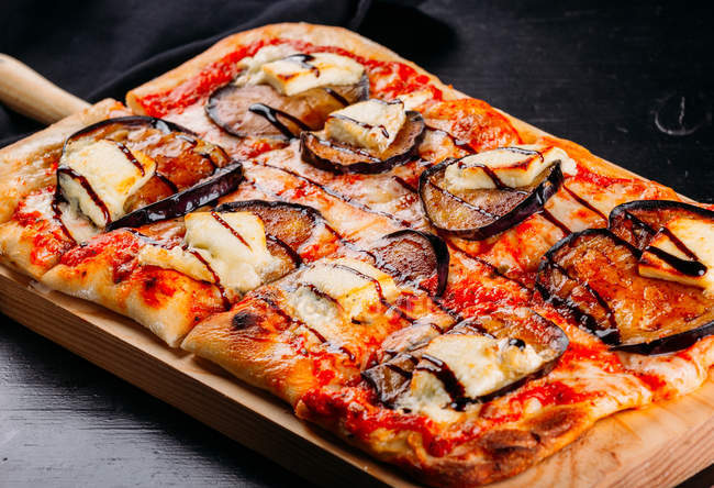 Close-up of cut pizza with cheese, sauce and sliced eggplants on wooden board on dark table — Stock Photo