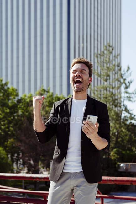 Возбужденный человек Холдинг смартфон и радость победы стоя на улице современного города — стоковое фото