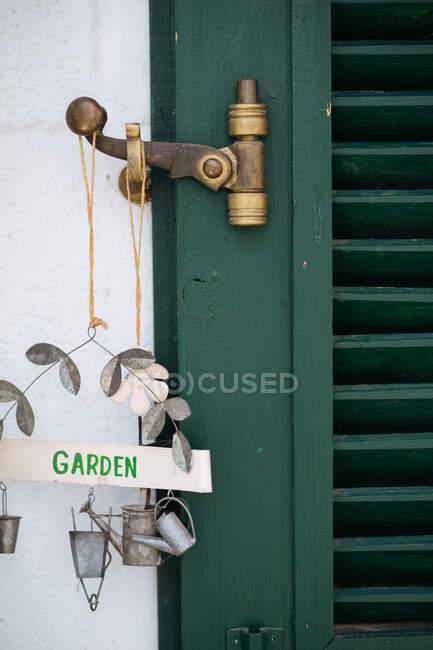 Vista close-up da velha porta de madeira verde rústica com trava de bronze desgastada e belo sinal de jardim de metal com regador e figuras de balde penduradas a partir dele na parede rebocada branca — Fotografia de Stock