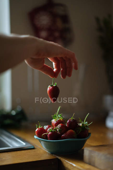 Human hand elegantly taking stem of ripe juicy strawberry from bowl of berries on wooden table — Stock Photo