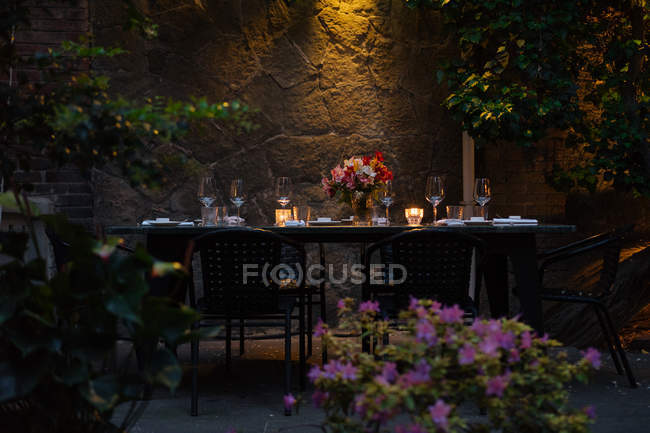 Setting table decorated with candles and flowers at night on backyard — Stock Photo