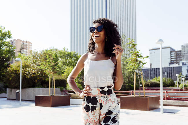 Elegant African-American woman walking on street of modern city on sunny day — Stock Photo