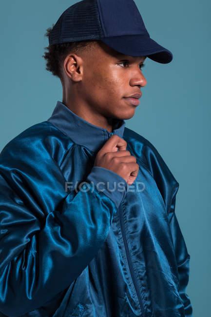 Ethnische Mann trägt glänzende blaue Bomberjacke und Mütze vor blauem Hintergrund — Stockfoto