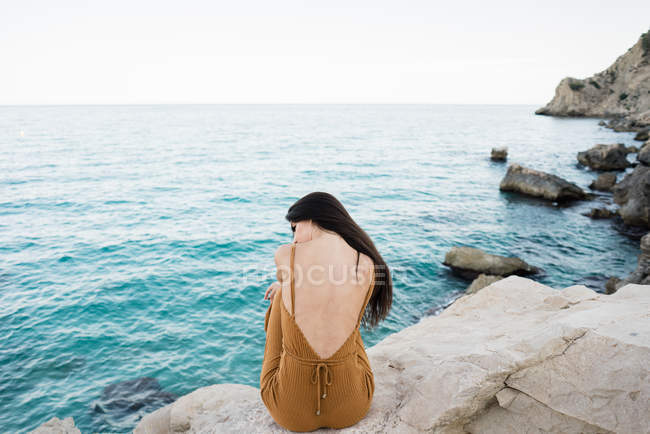 Rear view of woman with long hair sitting on rocky shoreline — Stock Photo