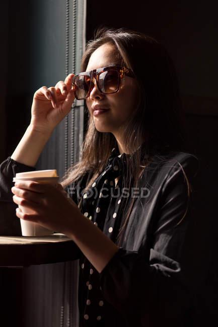 Mulher elegante em óculos de sol e lenço segurando xícara de papel de café e inclinação na mesa — Fotografia de Stock