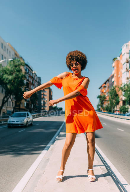 Beautiful black woman in bright dress standing on urban road and performing funny dance movement — Stock Photo