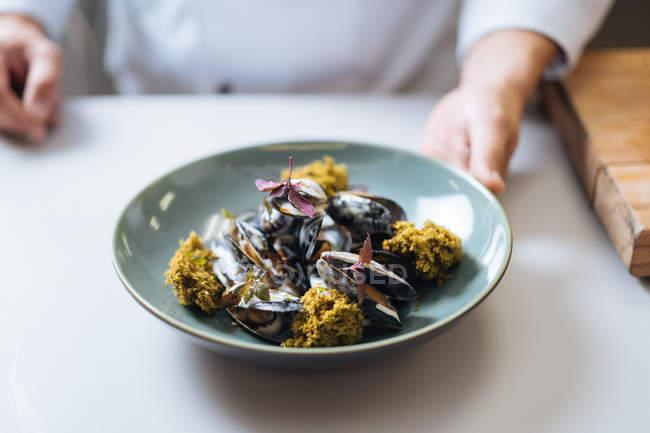 Шеф-повар блюдо северных морепродуктов с мидиями и сливочным соусом на тарелке крупным планом — стоковое фото
