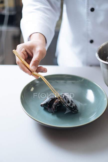 Primer plano del chef que sirve plato de mariscos nórdicos con mejillones en el plato - foto de stock