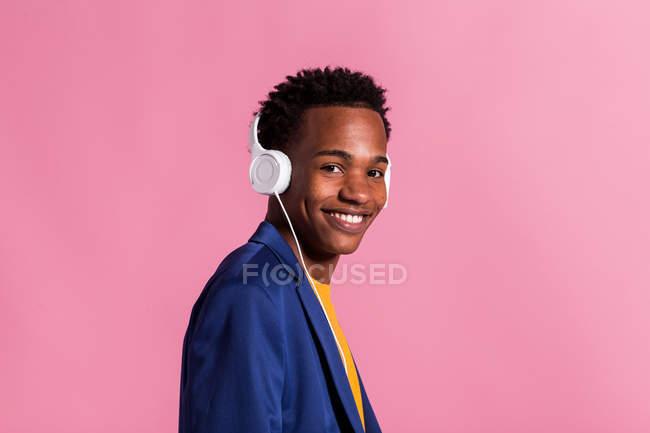 Портрет молодого черного мужчины в куртке и наушниках, улыбающегося в камеру на розовом фоне — стоковое фото