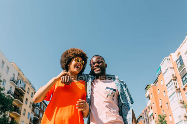 Low angle view of African American couple laughing and hugging while standing in city street — Stock Photo