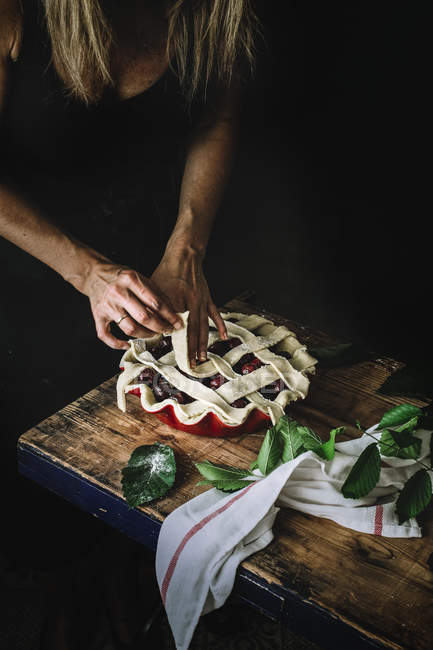 Cropped shot of woman creating lattice pie crust with straps of dough covering form with filling — Stock Photo