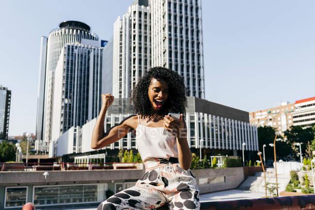 Возбужденных элегантная женщина Холдинг смартфон и радость победы стоя на улице современного города — стоковое фото