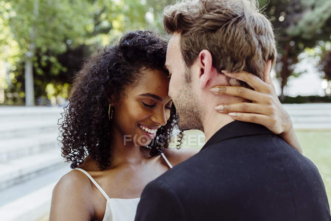 Attractive smiling woman standing in park and touching boyfriend neck — Stock Photo