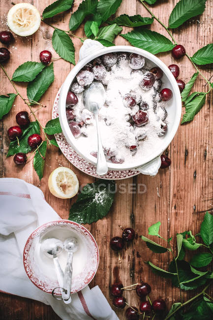 Flat lay of ceramic bowl filled with sugar covered cherries with green leaves on rustic table — Stock Photo