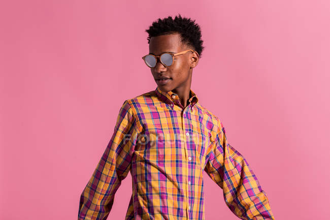 Stylish hipster in sunglasses and checkered shirt on pink background — Stock Photo