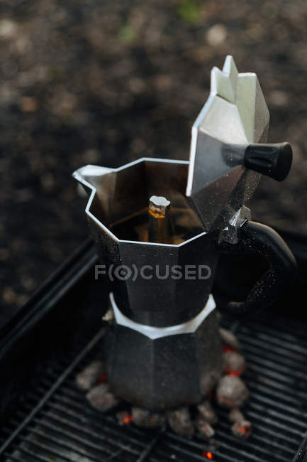 Coffee in coffee maker on top of warm charcoal in griddle — Stock Photo