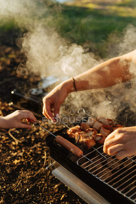 Человека руки подготовляя бекон и сосиски на шпажки гриль на сжигание угля в переносной гриль на открытом воздухе — стоковое фото