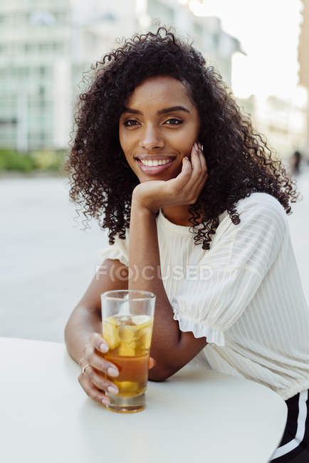 Charming African-American woman holding glass of beverage in outdoor cafe — Stock Photo