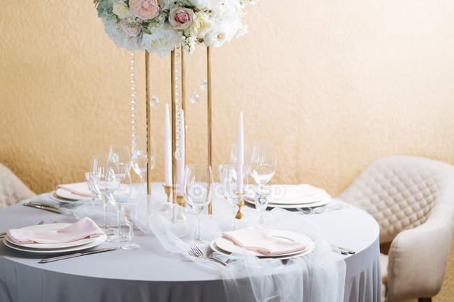 Круглі настройки таблиці в елегантному стилі з білим порцеляни, кришталю окуляри і букет — стокове фото
