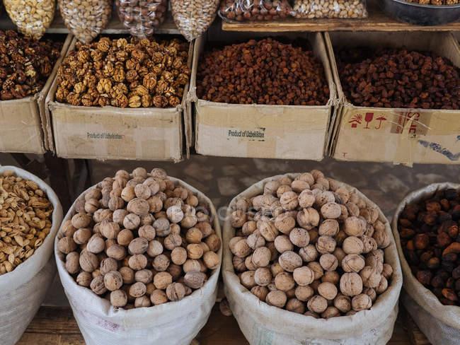 Säcke und Kisten gefüllt mit verschiedenen Nüssen und Gewürzen auf Bauernmarkt — Stockfoto