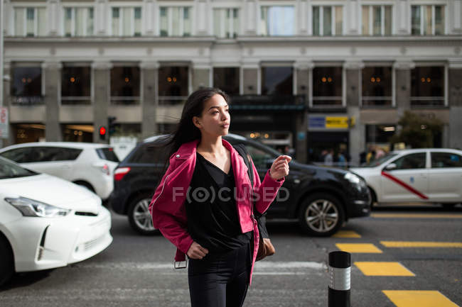 Trendy young woman in pink leather jacket walking on street with cars — Stock Photo
