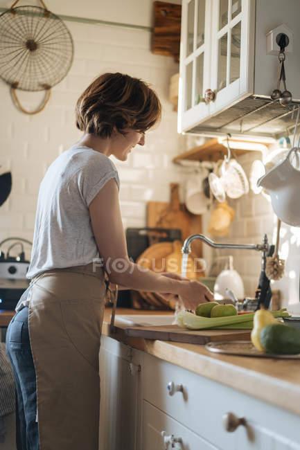 Frau waschen Sie Obst und Gemüse im Waschbecken unter Strom von Süßwasser in Küche — Stockfoto