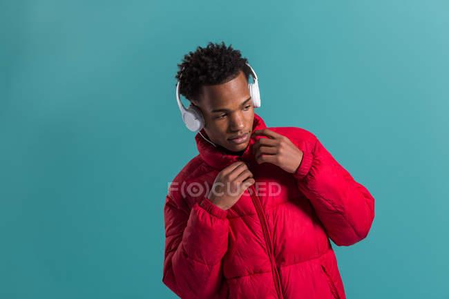 Élégant afro-américain dans le casque et les commandes veste puffy rouge sur fond bleu — Photo de stock