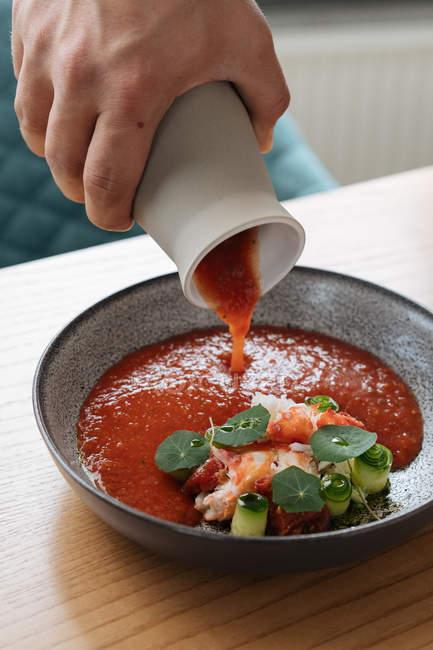 Крупный план человеческой руки лить традиционных северных красный суп украшенный травы в миске — стоковое фото