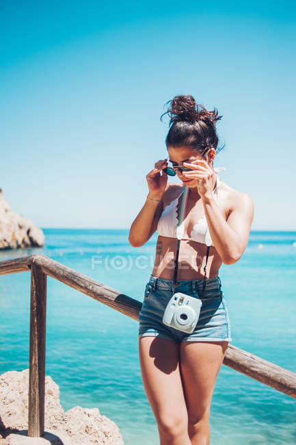 Young girl in summer clothes leaning on wooden handrail on beach — Stock Photo