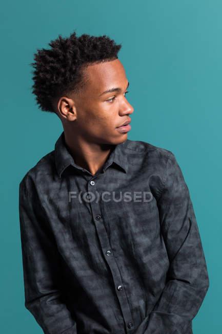 Réfléchie casual homme noir sur fond bleu — Photo de stock