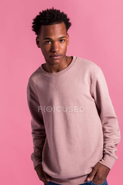 Hipster hombre negro posando sobre fondo rosa - foto de stock