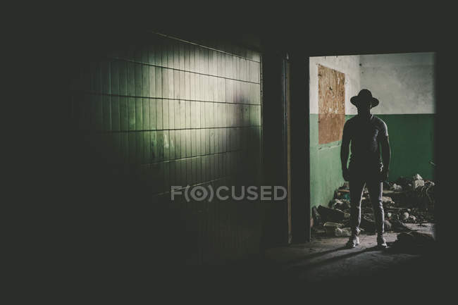 Dark male figure in hat standing in abandoned old building. — Stock Photo