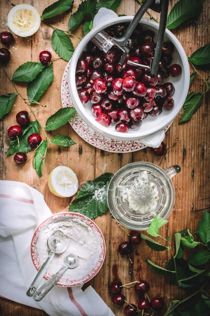 Lay flat di marasca e ciliegia pitter composto con foglie verdi, farina e limone sulla tabella rustica — Foto stock