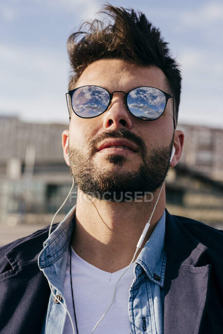 Stylish man relaxing with music on seafront — Stock Photo