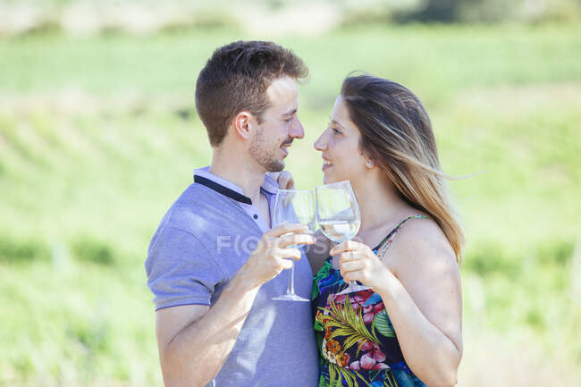 Side view of happy young couple with glasses of wine embracing and caressing tenderly while standing on landscape — Stock Photo