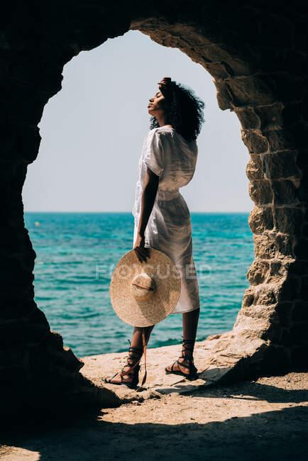 Mujer negra contemplando la vista al mar - foto de stock