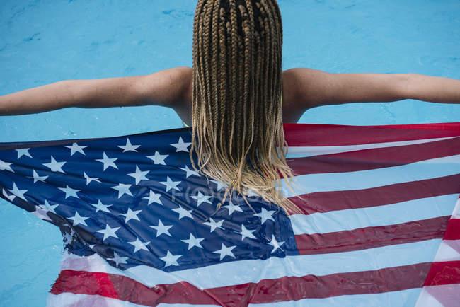 Visão traseira da mulher na piscina segurando bandeira americana — Fotografia de Stock