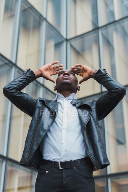 Jeune homme ethnique élégant en vêtements élégants et veste en cuir regardant vers le haut contre le bâtiment en verre moderne — Photo de stock