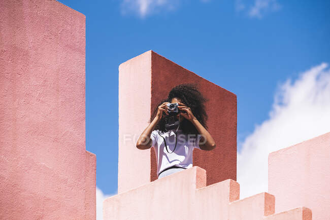 Black woman in a colorful geometric building taking a picture with a vintage camera — Stock Photo