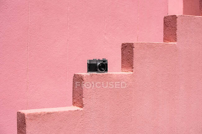 Vintage camera on pink stone building stairs — Stock Photo