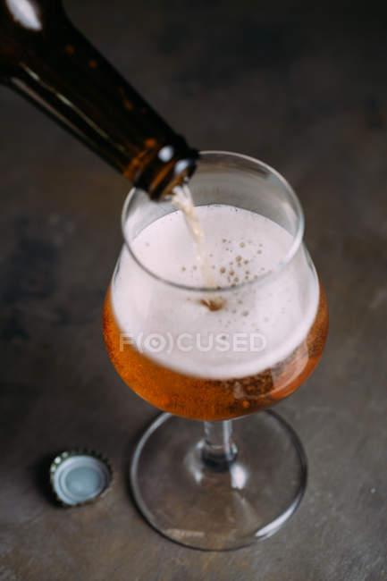 Bier aus Flasche auf grauem Hintergrund in Glas gießen — Stockfoto