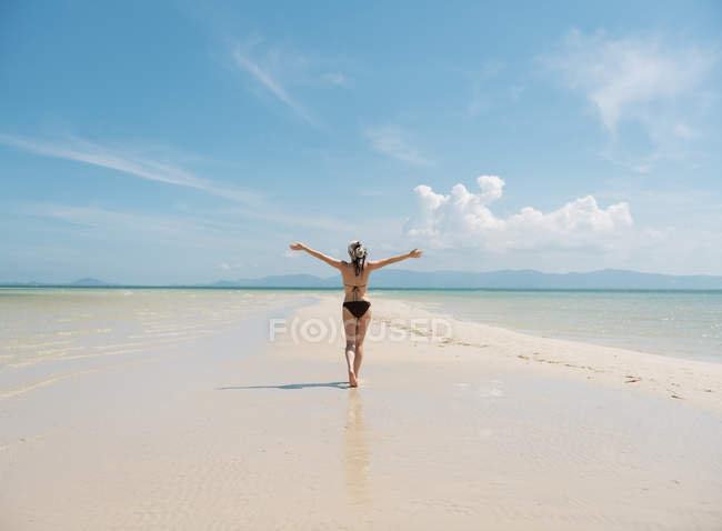 Woman in swimsuit walking on sandy coast at seaside in Thailand — Stock Photo